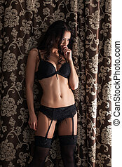Curly slender brunette posing in black lingerie on curtains...