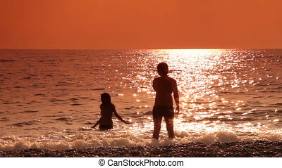 Teen couple on the beach - Silhouette of a young couple on...