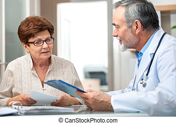 Medical exam - doctor talking to his female patient at...