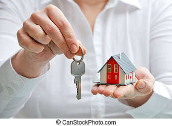 House and keys - Real estate agent with house model and keys