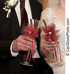 Bride and groom hold champagne in glasses for a toast