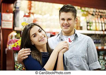 Couple holding lollipop