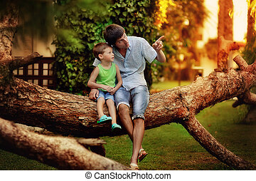 united family - Father and son have a rest on the big tree...