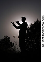 Muslim who prays standing with peace of mind - praying man...