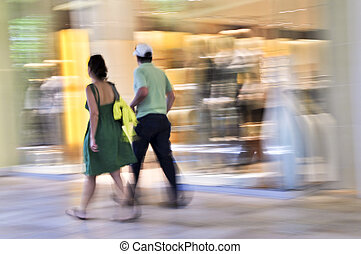 Shopping in a mall - Couple shopping in a mall, panning...