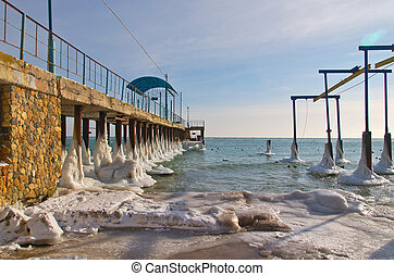 ice-covered pier and ducks in sea in winter
