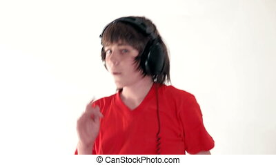Teenage boy listening music with headphones, dancing