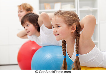 Kids and woman doing exercises with balls - Kids and woman...