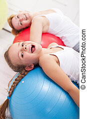 Happy exercising - little girl and her mother doing...