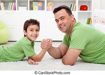 Father arm wrestling with his boy