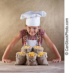 Little chef with pasta variety in bags