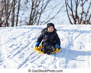 Sledding at winter time - Boy on sleigh Sledding at winter...