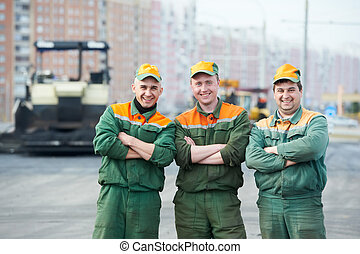 three asphalt road workers - three happy road construction...