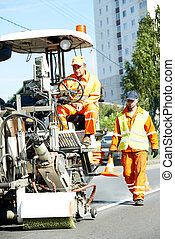 workers at road surface pavement markings - two construction...