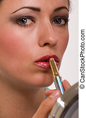 Applying lipstick - Close up of face of an attractive short...