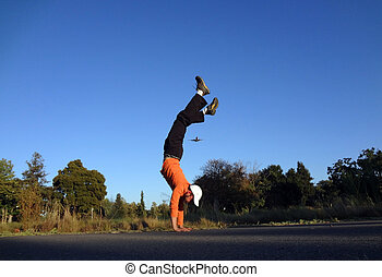 Man Handstands with plane flying in the sky above
