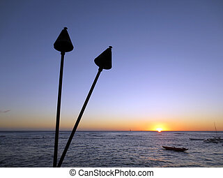 Sunset on Pacific Ocean with tiki torches and canoes