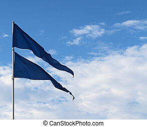 Blue triangular flags against sky - Pair blue flags blowing...