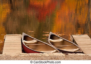 Two Boats - Two boats or canoes sitting in a lake during the...