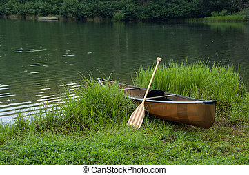 Boat with Paddle - Lone boat sitting on the shore of a...
