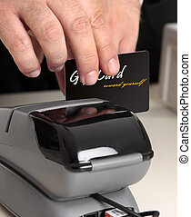 Swiping a card through a terminal - Man swiping a gift card,...