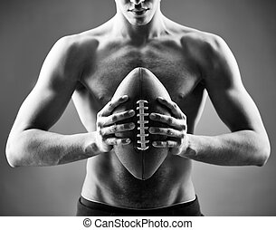 Rugby player - Close-up of topless man holding rugby ball in...