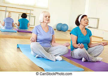 In pose of lotus - Portrait of two aged females doing yoga...