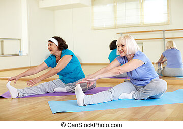 Good stretch - Portrait of sporty mature females doing...