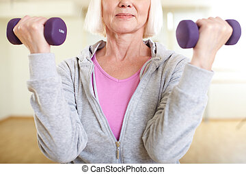 Having workout - Close-up of aged woman doing exercise with...