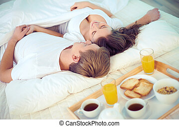 Lazy morning - Happy female and her husband relaxing on bed...