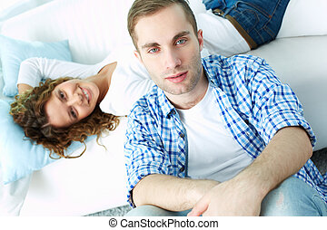 Man and his wife - Young man sitting on the floor and...