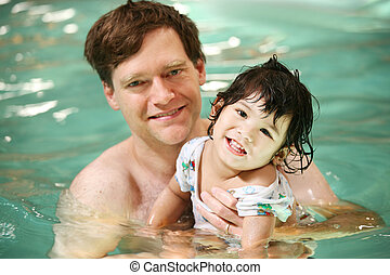 Father and toddler boy swimming in pool. Child has cerebral...