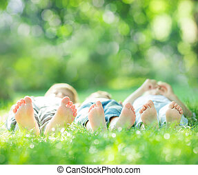 Family lying on green grass - Happy family lying on green...
