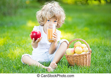 Healthy eating concept - Happy child sitting on green grass...