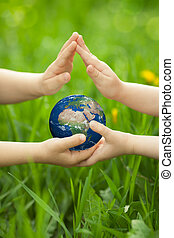 Planet Earth in children`s hands against green spring...