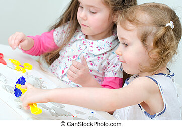 Two little girls sculpting using clay