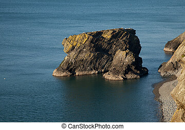 Sea stack. - The sea stack Trwyn y Tal and a pebble shore,...