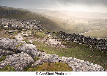 View of misty Malham Dales from limestone pavement above Malham Cove in Yorkshire Dales National Park