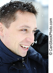Young male adult speaking on phone at winter snow time