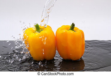 yellow paprikas - two yellow paprikas are pouring water