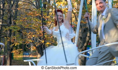 Newly married couple on swing in autumn park