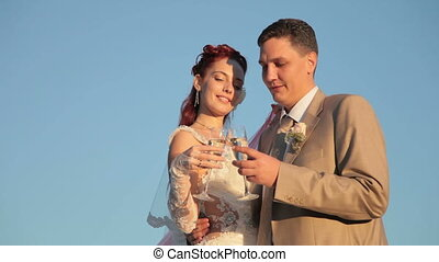Newlyweds with glasses of champagne against the blue sky