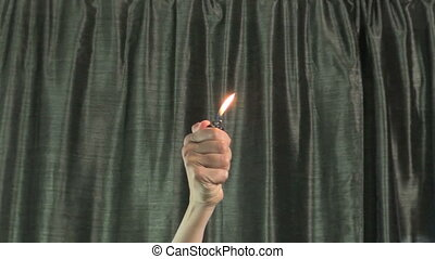 woman hands moving fired lighter with green curtain at...
