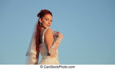 Bride with a glass of champagne against the blue sky