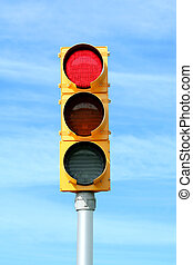 Red traffic signal light on blue sky