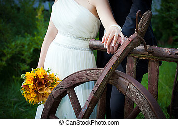 Young married couple holding hands - with wedding bouquet