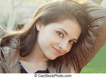 Beautiful thinking woman outdoors sunny day background...