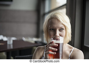 Blonde Woman with Beautiful Blue Eyes Drinking Glass of Pale...