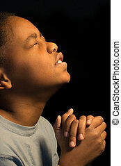Praying African Americn boy - A boy fervently prays to God.