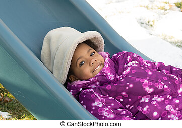 Winter fun - A young African-American girl laying on a slide...